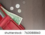Small photo of On the brown surface is a red purse with a dollar and credit cards, alongside small coins. Cash settlement, the price of the issue, lack of money.