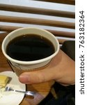 Small photo of Right hand holding black Americano coffee