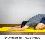 man doing yoga child pose on... | Shutterstock . vector #763199809