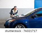 A man cleaning a car. - stock photo
