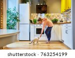 Stock photo happy woman stroking her charming cat while standing in her kitchen 763254199