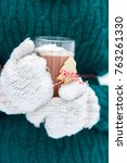 hands in wooly mittens holding... | Shutterstock . vector #763261330