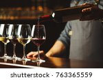 bartender pours red wine in... | Shutterstock . vector #763365559