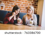 two women consuming sweet... | Shutterstock . vector #763386700