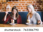 two women eating a snack with... | Shutterstock . vector #763386790