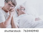 Small photo of Sad elderly woman taking care of her dying husband with alzheimer's