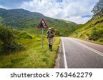 Small photo of Active man with a red rucksack is walking afoot along a road in the mountains of Scotland, summer time.
