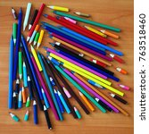 Small photo of lot of colored pencils scattered on a wooden table with a heap of heaps