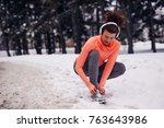 young sportswoman lacing her...   Shutterstock . vector #763643986