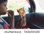 child eating pizza in the car | Shutterstock . vector #763650100