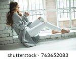 woman in a sweater drinking tea  | Shutterstock . vector #763652083