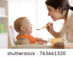 mother spoon feeding her baby...   Shutterstock . vector #763661320