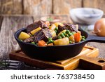 Small photo of Beef and vegetable stew with potatoes in cast iron skillet on rural table