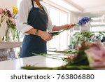 female florist creating bouquet ... | Shutterstock . vector #763806880