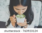 Young Woman Drinking Hot Green...
