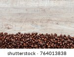 coffee beans on wood background | Shutterstock . vector #764013838