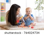woman and baby playing musical... | Shutterstock . vector #764024734