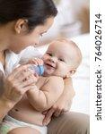 mother giving baby son water... | Shutterstock . vector #764026714