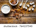 Small photo of lumps of white and brown sugar on wooden table background top view
