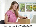 Small photo of Woman At Home Writing Address On Package