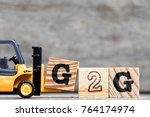 Small photo of Yellow plastic forklift hold letter G to complete word G2G (Government to government) on wood background