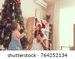 Mother and daughter playing on the floor next to a nicely decorated Christmas tree, making soap bubbles and having fun