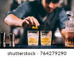 Stock photo barman adding cocktail ingredients on whiskey cocktails on bar counter 764279290