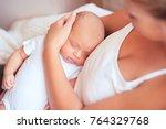 sleeping baby in mothers hands... | Shutterstock . vector #764329768