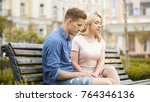 Small photo of Couple feeling awkward, sitting on bench in silence, crisis in relationship