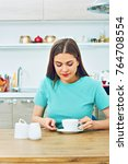 woman sitting at kitchen with... | Shutterstock . vector #764708554