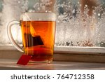 Stock photo a tea bag in a mug a mug of tea on the balcony window sill in winter cold on the glass is a frost 764712358