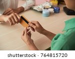 Small photo of Hands of receptionist taking card to accept payment