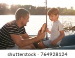 father with son fishing from... | Shutterstock . vector #764928124