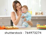 mother feeding baby with spoon... | Shutterstock . vector #764973274