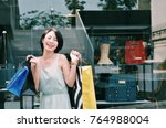 asian woman holding shopping at ... | Shutterstock . vector #764988004