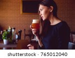 young brunette drinking a beer...   Shutterstock . vector #765012040