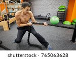 man pulls fitness rope in gym... | Shutterstock . vector #765063628