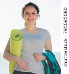 Small photo of Young girl ready to begin usual training on beach by sea