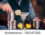 bartender garnishing drink ... | Shutterstock . vector #765147283