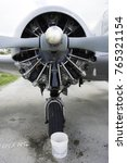 Small photo of An aircraft engine with a bucket positioned below to catch leaking fluids such as oil.