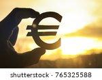 euro symbol in hand on sunset... | Shutterstock . vector #765325588