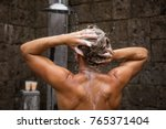 man washing hair in shower | Shutterstock . vector #765371404