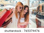 two smiling shopaholic women... | Shutterstock . vector #765374476