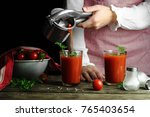 a woman pours tomato juice from ... | Shutterstock . vector #765403654