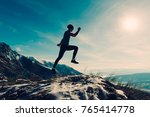 young man jumps on the mountain | Shutterstock . vector #765414778