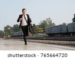 Small photo of Young asian businessman running to at train station in hand holding a suitcase laptop and wearing formal suit in a rush hour to work. Hurry time.