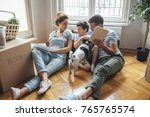 Stock photo husband and wife and their son and a pet moving in new home 765765574