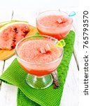 Small photo of Jelly airy watermelon in two glass bowls, a spoon on a green towel on a wooden plank background