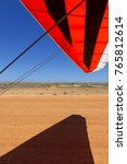 Small photo of The wingtip of an ultralight on takeoff on a gravel airstrip
