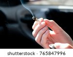 detail of a woman hand holding a curling cigarette